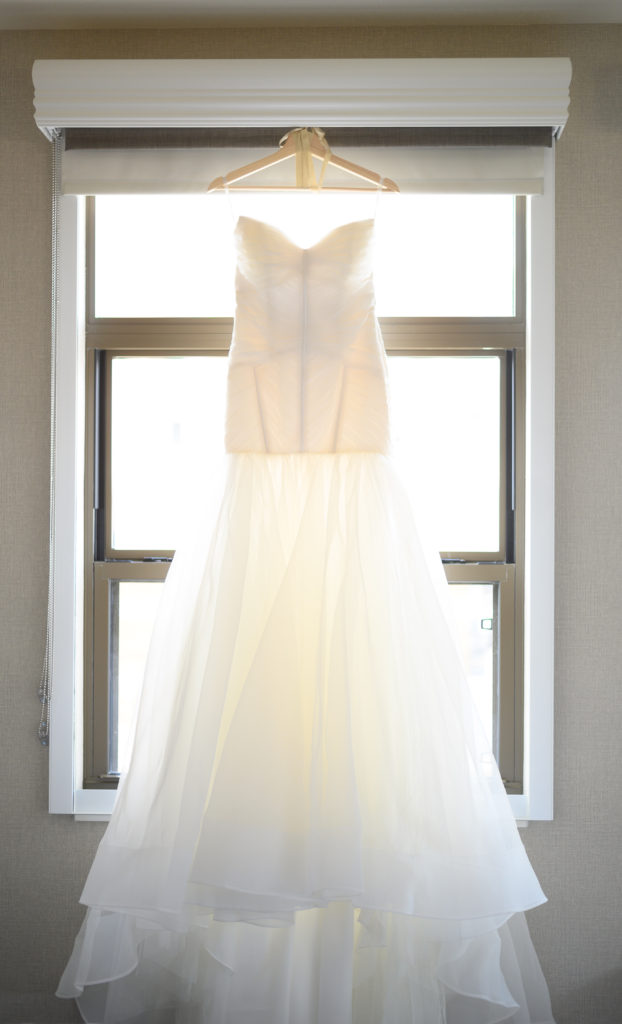 dress hanging in window maryland wedding planner statuesque events